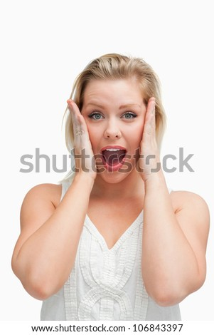 Surprised blonde woman standing with her mouth opened against a white background - stock photo