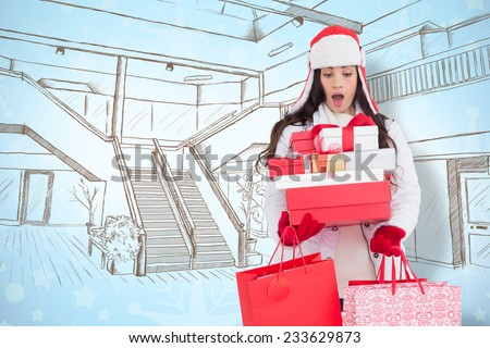 Surprised brunette in winter clothes holding many gifts and shopping bags against snowflake wallpaper pattern - stock photo
