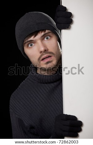 surprised burglar looking behind the door - stock photo