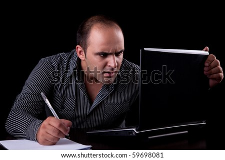 surprised businessman looking to computer and taking notes, isolated on black background. Studio shot. - stock photo