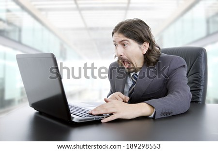 surprised businessman working with is laptop at the office - stock photo