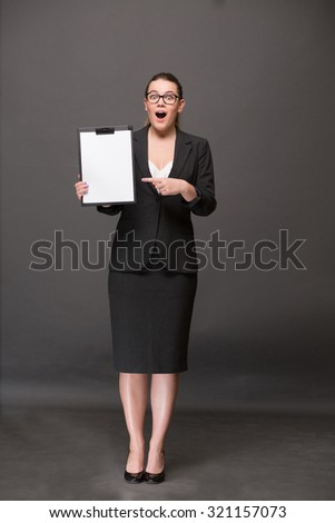 Surprised businesswoman holding a clip board with blank page and pointing out. Lady in full length showing her emotions: amazement, excitement, etc. - stock photo