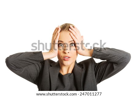 Surprised businesswoman holding hands on chin. - stock photo