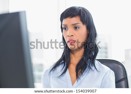 Surprised businesswoman looking at her computer in office - stock photo