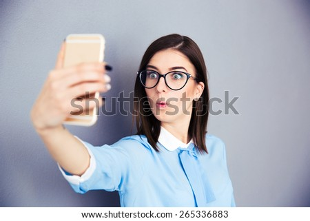Surprised businesswoman making selfie photo on smartphone. Wearing in blue shirt and glasses. Standing over gray background - stock photo
