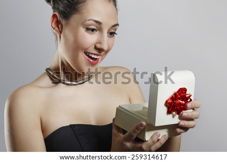 Surprised cheerful woman opening gift box - stock photo