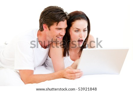 Surprised couple using a computer lying on their bed at home - stock photo