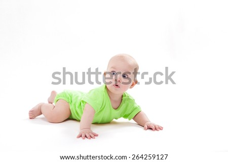 Surprised cute baby lying on his stomach and looking at the camera, picture with depth of field - stock photo