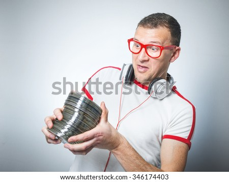 Surprised dj or party young man holding lot cds.Studio shot - stock photo