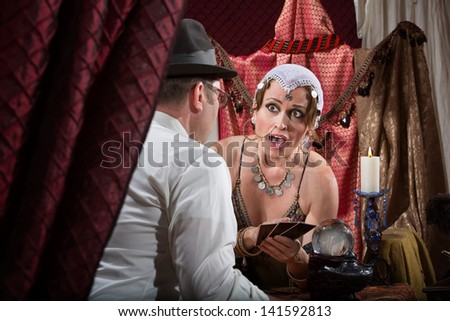 Surprised fortune teller with customer and tarot cards - stock photo