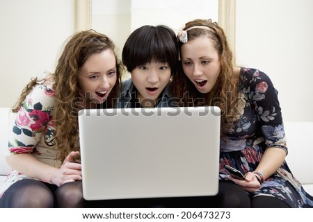 Surprised friends looking at something in laptop - stock photo