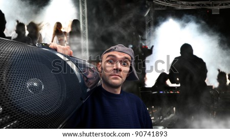 Surprised funny man with boom box on his shoulder dancing on disco - stock photo