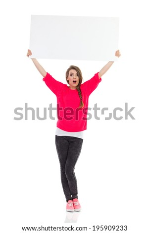 Surprised girl holding blank banner over her head. Full length studio shot isolated on white. - stock photo