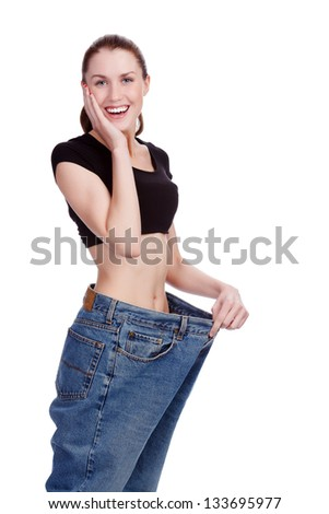 Surprised girl in big jeans. White background - stock photo