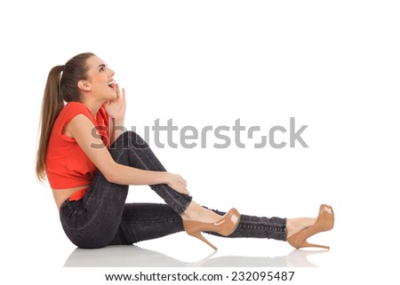Surprised girl in red top, black jeans and high heels sitting on the floor, holding hand on chin and looking up. Full length studio shot isolated on white. - stock photo