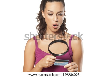 surprised girl looking at her credit card using a magnifying glass - stock photo
