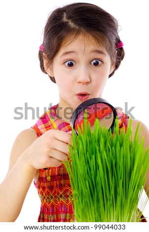 Surprised girl looking at the grass through a magnifying glass, isolated on white - stock photo