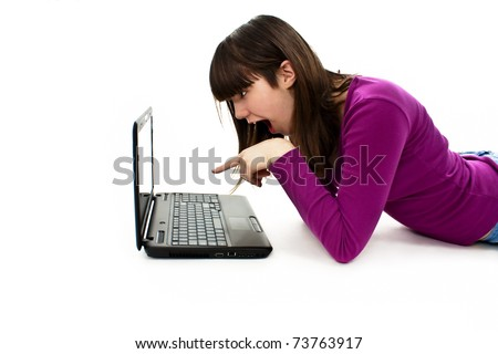 Surprised girl lying down on the floor with her laptop. Pointing at it. Over white - stock photo