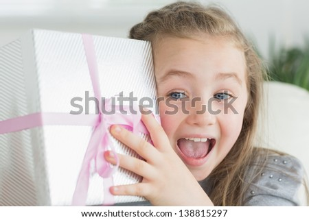 Surprised girl shaking a present to guess whats inside - stock photo