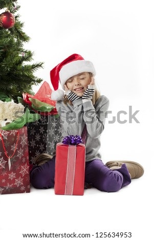 Surprised girl with her christmas gift with eyes closed - stock photo