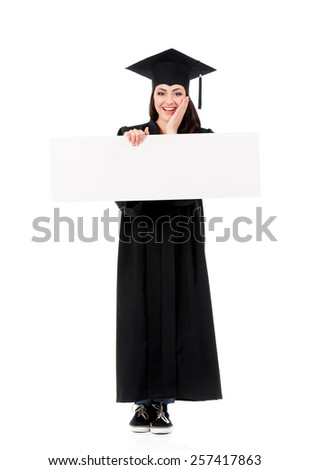 Surprised graduate girl student in mantle showing blank placard board, isolated on white background - stock photo