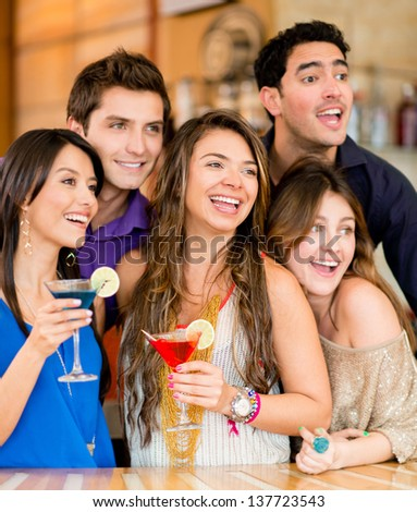 Surprised group of people at the club holding drinks - stock photo