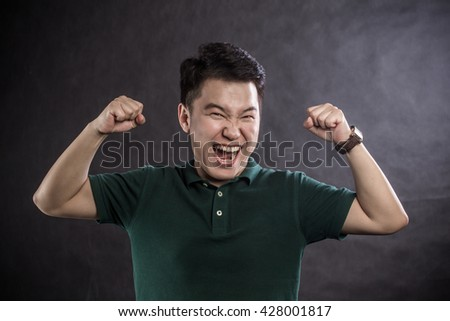 Surprised happy young man with beard pointing up with both hands over chalkboard background - stock photo
