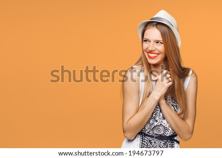 Surprised happy young woman looking sideways in excitement. Isolated over orange background - stock photo