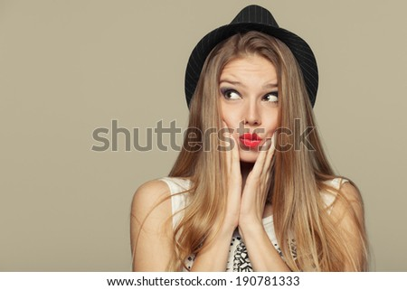 Surprised happy young woman looking up in excitement. Fashion girl in hat. isolated on beige background - stock photo