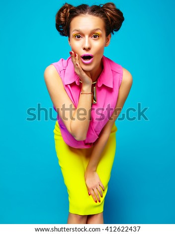 surprised hipster girl in casual colorful vivid hipster yellow and pink summer clothes on blue background  - stock photo