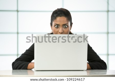 Surprised Indian Business woman working on her laptop. - stock photo