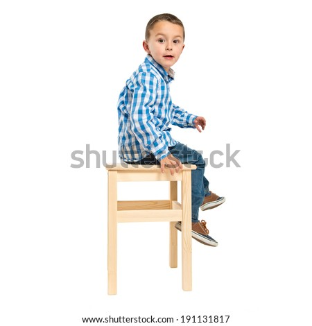 Surprised kid sitting on a wooden chair over white background  - stock photo