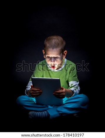 Surprised kid with tablet computer - stock photo