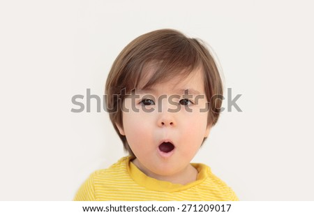 Surprised little boy. Shocked toddler, with mouth gaping open on neutral background. Horizontal image of young child with expression of disbelief. Preschooler with funny face. Kid that looks amazed. - stock photo