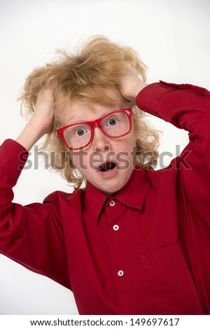 Surprised little boy.  Surprised red hair boy in glasses holding his head in hands and looking at camera while isolated on white - stock photo