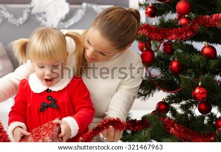 Surprised little girl opening present under christmas tree. - stock photo