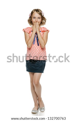 Surprised little girl standing with hands over mouth, over white background - stock photo
