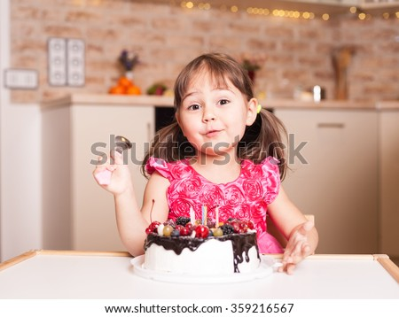 surprised little girl with cake and spoon - stock photo