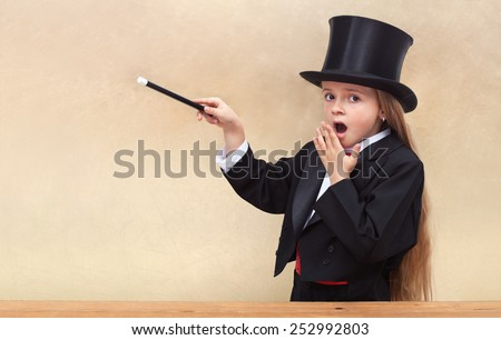 Surprised magician girl with magic wand - copy space on golden background- shallow depth of field - stock photo