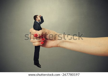 surprised man clamped in big female fist and looking up with misunderstanding against dark background - stock photo