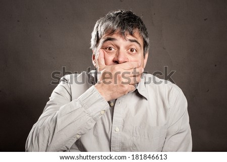 surprised man covering mouth with his hand - stock photo
