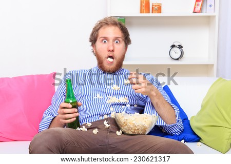 Surprised man eating popcorn on the sofa at home  - stock photo