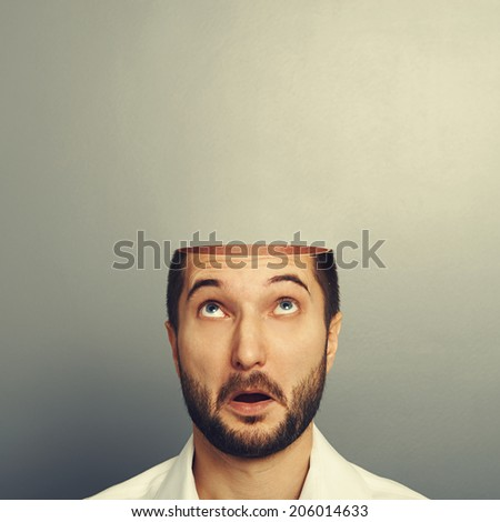 surprised man looking up at his open empty head. photo over grey background - stock photo