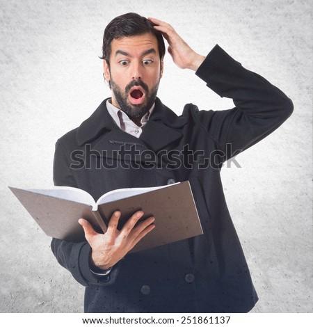 Surprised man reading book - stock photo