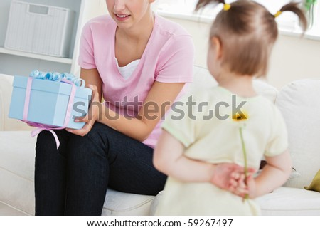 Surprised mother getting a present from her little daughter at home - stock photo