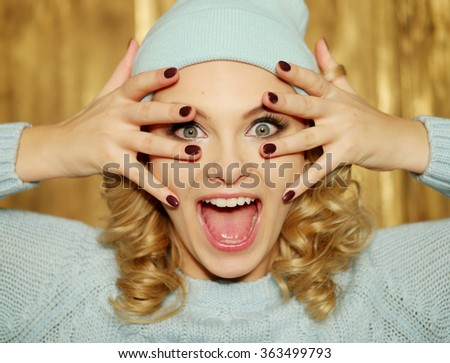 Surprised or shocked attractive young blond woman with ringlets and huge blue eyes holding her hands with manicured red nails over her mouth in a close up head shot - stock photo