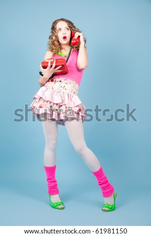 Surprised pin-up woman in colorful clothers standing on the blue background - stock photo