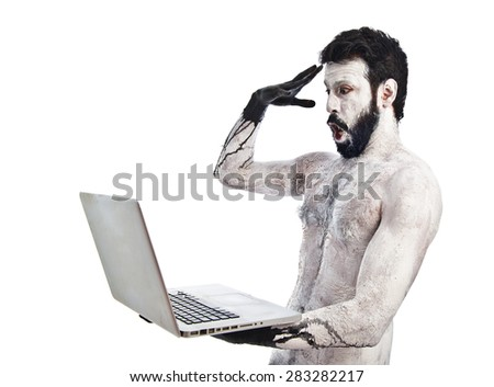 Surprised primitive with laptop - stock photo
