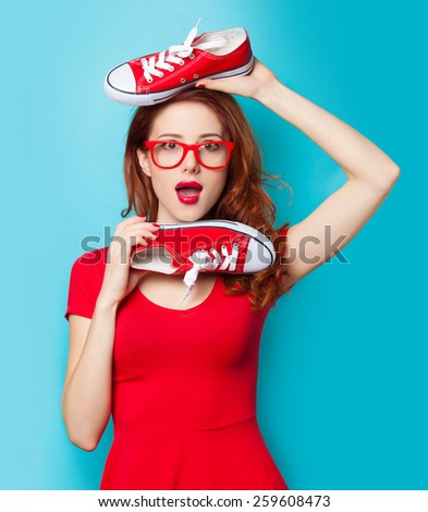 Surprised redhead girl in red dress with gumshoes on blue background. - stock photo
