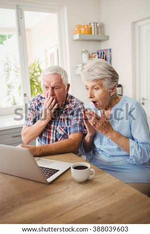 Surprised senior couple using laptop at home - stock photo